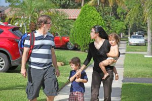 A happy family walks safely to their neighborhood school in the morning.